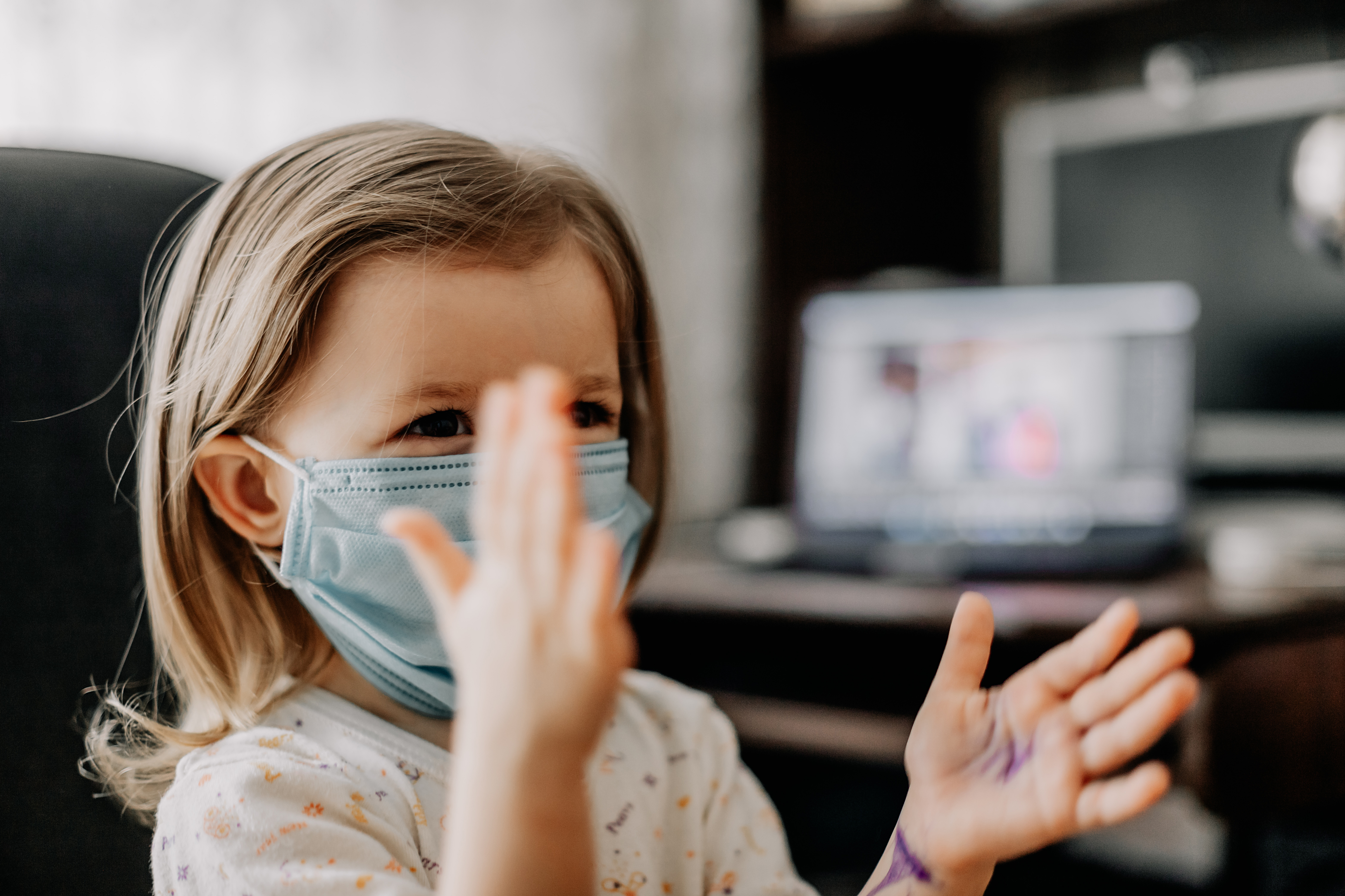 a young child wearing a protective medical mask is home treated at home