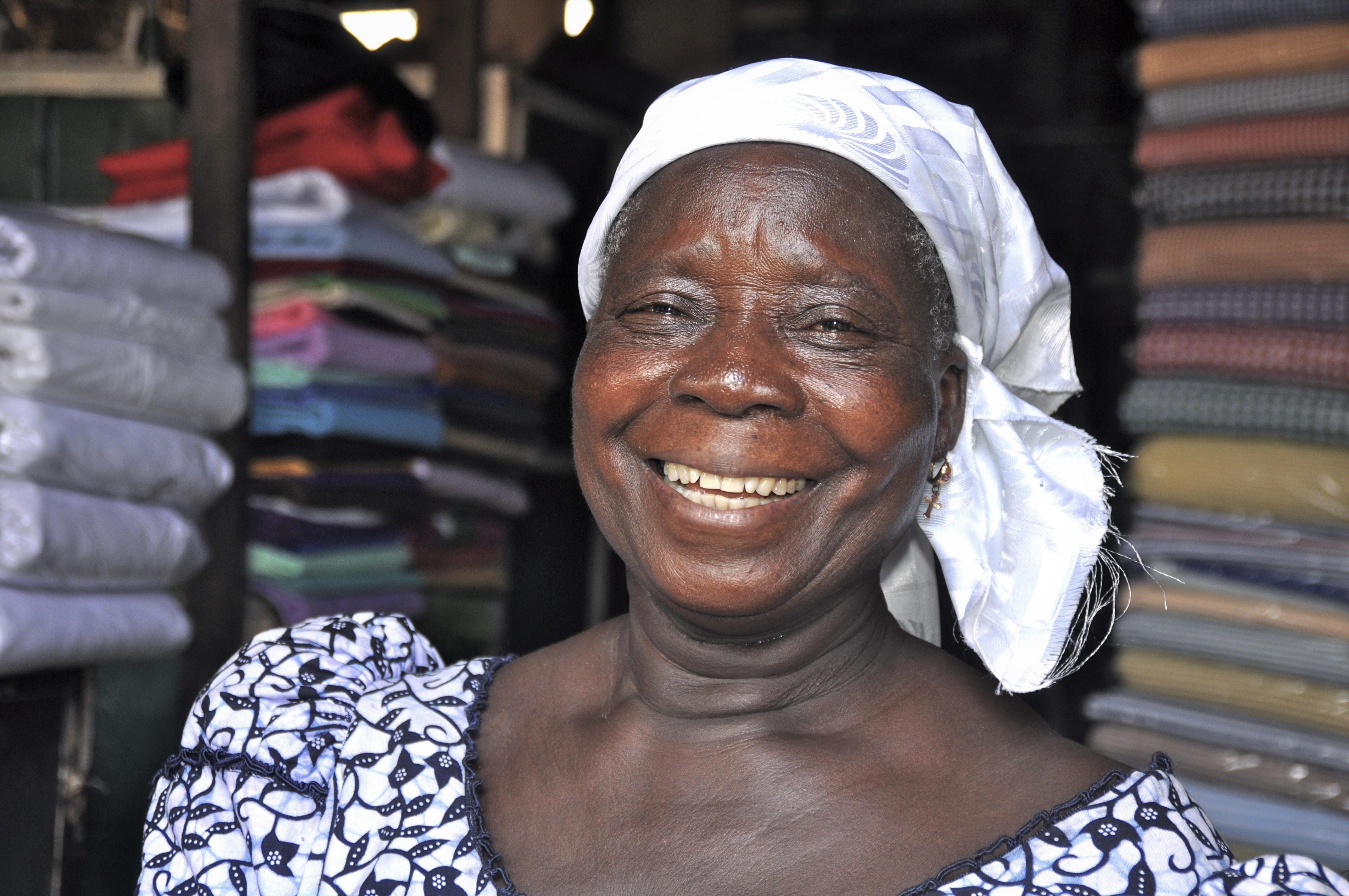 Lachende Frau vor ihrem Marktstand in Afrika